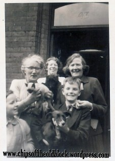 My grandfather Wm Boles's sister Jennie (in glasses) holds the little Siamese cat. She is standing next to her cousin Sophie Currie and Sophie's children. Undated image.