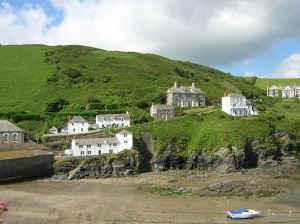 Port Isaac. The Doc's house/office stands on the hill to the left of the big stone house. (Wikimedia Commons: public domain by Sbeech)