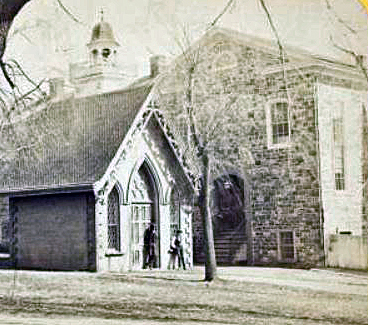 Old Moravian Chapel (est. 1751) & dead house (in the foreground). Wikimedia Commons: Image from NYPL collections is in public domain). Image date unknown-between 1865-1875 (?)